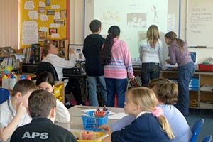 Primary classroom in UK with students using interactive whiteboard